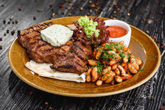 Medium rare grilled beef steak on on wooden black background on  brown plate Royalty Free Stock Image