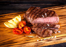 Steak Ribeye. Medium rare grilled Steak Ribeye with fried onions and cherry tomatoes on a wooden board Stock Photo