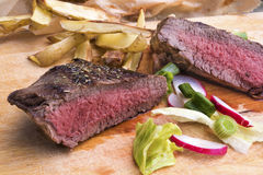 Medium rare grilled top rump steak with roasted potatoes Royalty Free Stock Photography