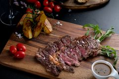 Medium rare meat rib eye steak slices in pan on chopping wooden royalty free stock photos