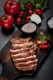 Medium rare meat rib eye steak slices in pan on chopping wooden royalty free stock photography