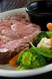 Medium rare steak. With au jus and steamed vegetables stock photos