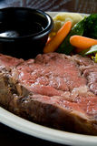 Medium rare steak. With au jus and steamed vegetables stock image