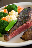 Medium rare steak. With steamed vegetables royalty free stock image