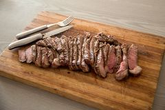 Medium Rare Steak. Grilled and cut up to be served on a chopping board stock photo