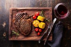 Medium rare Steak Ribeye with corn and cherry tomatoes. Medium rare grilled Steak Ribeye Black Angus with corn and cherry tomatoes on serving board block on royalty free stock images