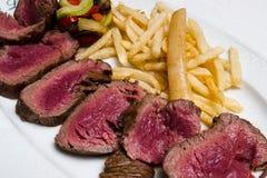 Medium rare steak with vegetables. Medium rare steak with fried vegetables and potatoes royalty free stock photos