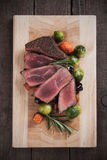Medium rare steak on wooden board. Medium rare beef steak with carrrot and brussel sprout on wooden table stock images