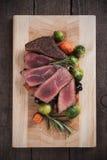 Medium rare steak on wooden board Stock Images
