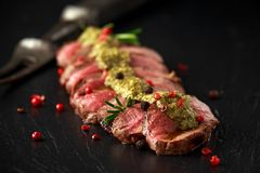 Medium rare venison steak with green pesto sauce and pepper royalty free stock photography
