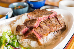 Medium rare wagyu beef steak. With Japanese rice and vegetable salads on the side Royalty Free Stock Images