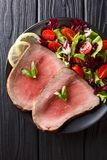 Medium roasted beef steak with vegetable salad close-up on a plate. vertical top view. Medium roasted beef steak with vegetable salad close-up on a plate on a royalty free stock photos