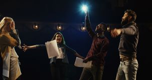 Actors celebrating on stage. Medium shot of actors and actresses throwing scripts away and hugging while celebrating on stage in a theater stock footage