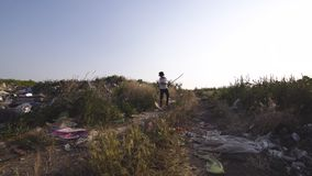 Angry boy walking in dump. Medium shot of angry boy walking in dump and hitting grass stock video footage