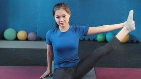 Medium shot Asian smiling fitness woman doing stretching raising legs making pilates exercise