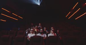 Audience watching comedy movie in cinema. Medium shot of audience laughing while watching comedy movie in a cinema stock video
