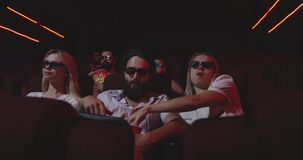 Audience watching comedy movie in cinema. Medium shot of audience laughing while watching comedy movie in a cinema stock footage