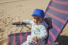 Medium shot baby boy with a blue cap sit in a plastic chair at t Royalty Free Stock Image