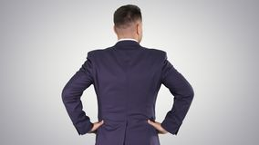 Businessman looking around with hands on hips on gradient background. Medium shot back view. Businessman looking around with hands on hips on gradient stock video footage