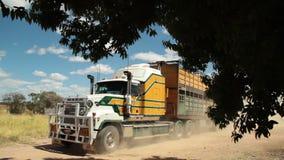 Huge truck carrying a long cargo. A medium shot of a big yellow truck carrying over a long cargo stock footage