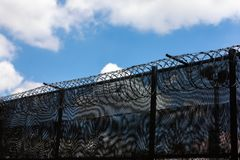Medium shot of boarder wall. With razor wire and blue sky and clouds above Stock Photography