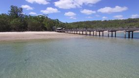 Beach and boat with forest trees. A medium shot of a boat and blue ocean. Camera moves forward to show a bridge and pans to left to view a beach and shoreline stock video footage