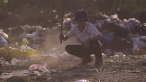 Boy crouching in dump. Medium shot of boy crouching and making dust by stick in dump stock footage