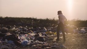 Boy in dump. Medium shot of boy kicking dust and hitting garbage in dump stock video