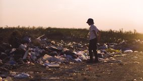 Boy kicking dust in dump. Medium shot of boy kicking dust and hitting garbage in dump stock footage