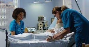 Boy lying in hospital bed. Medium shot of a boy lying in hospital white two nurses caring him stock footage