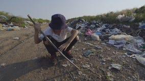 Boy poking ground with stick