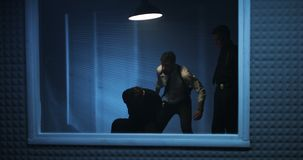 Policemen using excessive force during interrogation. Medium shot of a brutal policeman choking a drug dealing suspect with a plastic bag then kicking him to the stock video footage