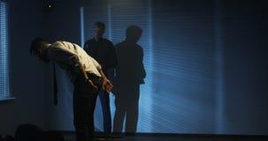 Policemen using excessive force during interrogation. Medium shot of brutal policemen using excessive force during interrogation of a drug dealing suspect stock video