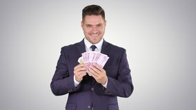 Business man showing euro banknotes smiling on gradient background. Medium shot. Business man showing euro banknotes smiling on gradient background stock video