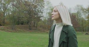 Medium shot. Caucasian blond woman slomo walking toward fall woods.Following side gimbal.Storytelling real young adult stock video footage