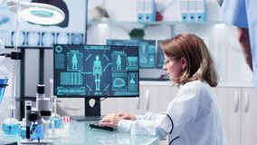 Medium shot of chemist woman working on the computer. While the displays shows a modern body scan stock footage