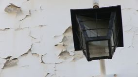 Cracked wall with lamp. A medium shot of cracked wall with lamp. Camera pans to the right stock video footage