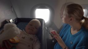 Baby in a cot on an airplane. Medium shot of a cute baby in a baby cot bassinet on board an airplane while her mother checks her cellphone stock footage
