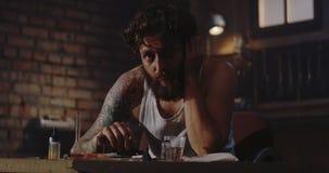 Depressed drug addict staring away. Medium shot of a depressed drug addict sitting at a table and looking away stock footage