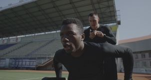 Trainer encouraging disabled athlete. Medium shot of a disabled athlete rolling with wheelchair while being encouraged by his trainer stock video footage