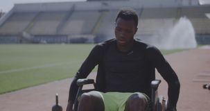 Trainer encouraging disabled athlete. Medium shot of a disabled athlete rolling with wheelchair while being encouraged by his trainer stock footage