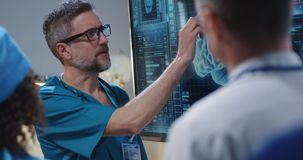Doctor explaining diagnosis to colleagues. Medium shot of a doctor explaining diagnosis to his colleagues at a digital screen with a 3D image of a brain stock photography