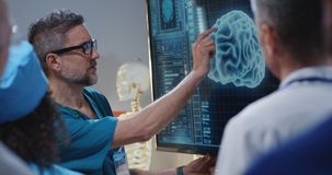 Doctor explaining diagnosis to colleagues. Medium shot of a doctor explaining diagnosis to his colleagues at a digital screen with a 3D image of a brain royalty free stock photography