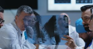 Doctors analyzing cervical spine x-ray. Medium shot of doctors analyzing cervical spine x-ray during a meeting stock video