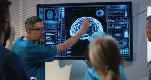 Doctors discussing diagnosis. Medium shot of a doctors discussing brain damage diagnosis at a digital screen with a 3D image of a brain stock footage