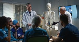 Doctors explaining diagnosis to their colleagues. Medium shot of doctors explaining diagnosis to their colleagues with a cervical spine x-ray and a skeleton stock video