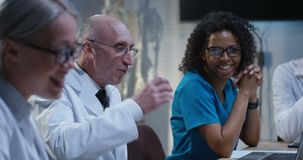Doctors having a meeting. Medium shot of doctors having a cheerful conversation during a meeting stock footage