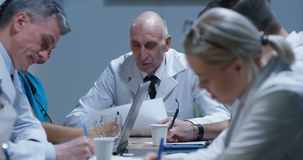 Doctors having a meeting. Medium shot of doctors talking and taking notes during a meeting stock video footage
