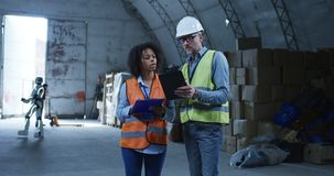 Engineers talking while robot working in the background. Medium shot of engineers talking while robot working in the background stock video footage