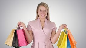 Excited pretty young lady standing looking camera showing shopping bags on gradient background. stock video footage
